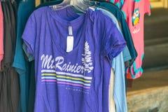 MER REGNIG MT, WA - AUGUSTI 16, 2017: Skjortor på en souvenir shoppar Mt Arkivbild