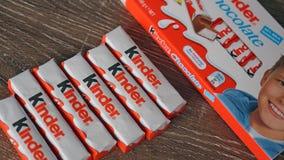 Mer snäll chokladstänger på ljus - brun träbakgrund Mer snäll stänger produceras av Ferrero som grundades i 1946 Royaltyfri Bild
