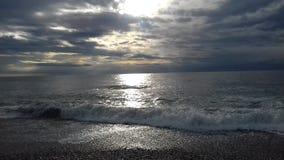 Mer tranquille avec des vagues de doux et soleil derrière des nuages Image stock
