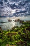 Mer tranquille avec la roche rugueuse et le ciel obscurci Photographie stock libre de droits