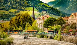 Merano Bolzano buses on bridge over river in mountain village. Buses on the bridge over the river in the mountain village of Meran - Bolzano, 11 Aug 2017 Royalty Free Stock Image
