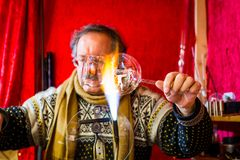 Merano, el Tyrol del sur, Italia - 16 de diciembre de 2017: Un hombre está haciendo las bolas de cristal de la Navidad en el merc Imágenes de archivo libres de regalías