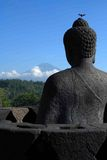 Merapi and Borobudur Statue. Statue overlooking the volcanoes in the indonesian budish tample Stock Photo