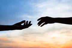 Mercê, silhueta de duas mãos no conceito do fundo, da conexão ou da ajuda do céu foto de stock