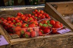 Mercado, comércio em produtos frescos Caixa de madeira com as morangos classificadas por bandejas foto de stock royalty free
