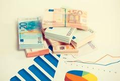 Mercado de acción, impuesto, concepto de la educación Papeles de cartas con la pila de cuentas euro de los billetes de banco Foto de archivo libre de regalías