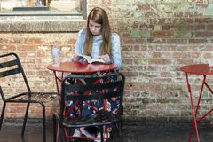 MERCADO de CHELSEA, NEW YORK CITY, los E.E.U.U. - 21 de julio de 2018: mujer joven hermosa en café que lee un libro foto de archivo libre de regalías