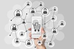 Mercado de Digitas e conceito móvel das vendas com a mão que guarda o telefone esperto moderno e a rede social dos consumidores ilustração stock