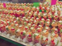 Mercado de la comida Contador con las tazas plásticas llenadas de una mezcla de pedazos de fruta fresca imagen de archivo libre de regalías