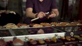 Mercado de pulgas asiático un hombre que hace la pulsera china tradicional metrajes