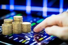 Mercado de valores de ação que olha com tabuleta e a pilha digitais de moeda de ouro imagem de stock