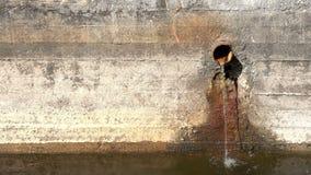 Mercado del agua del drenaje en muro de cemento sobre superficie del río almacen de video