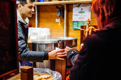 Mercado do Natal com os povos que compram o vinho ferventado com especiarias Imagens de Stock Royalty Free