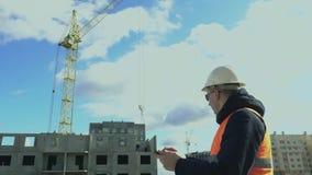 Mercado inmobiliario Construcci?n de edificios residenciales Ingeniero que trabaja en la tableta electrónica Constructor metrajes