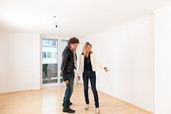 Pares jovenes que buscan las propiedades inmobiliarias Foto de archivo
