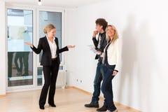 Pares jovenes que buscan las propiedades inmobiliarias con agente inmobiliario femenino Foto de archivo