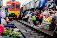 Mercado local raillway de Maeklong con el tren fotos de archivo