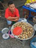Mercado local Trang, Tailandia - Desember 25, 2017: una venta del hombre foto de archivo