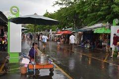 Mercado popular del fin de semana de Chatuchak durante la estación de lluvias con los visitantes que sostienen los paraguas