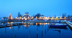 Mercado suíço bonito do Natal de switzerland na costa do lago com os navios cobertos de neve na hora azul fotos de stock