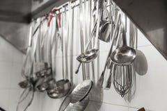 Mercadorias da cozinha que penduram de uma parede imagem de stock royalty free