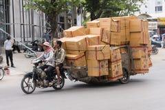 Mercancías del transporte de los trabajadores en moto y carro Imágenes de archivo libres de regalías