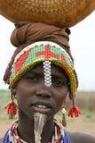 Mercancías que llevan de la mujer etíope en la pista Foto de archivo