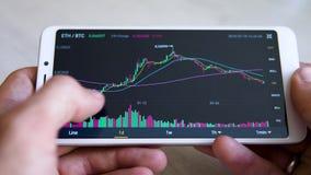 Mercato azionario, commerciale online Le mani del ` s degli uomini usano il app sullo smartphone per seguire il cryptocurrency archivi video