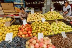 Mercato con le mele, l'uva ed i venditori femminili occupati aspettanti i clienti della frutta fresca Fotografia Stock
