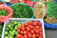 Mercato di strada asiatico che vende il pepe ed i verdi della calce del pomodoro Fotografie Stock Libere da Diritti