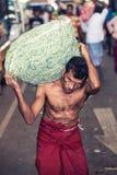 Mercato di verdure Lavoratore con il sacco pesante Immagini Stock