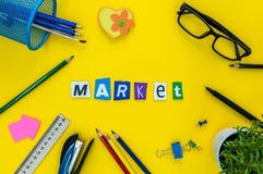 Mercato - testo delle lettere scolpite al fondo giallo della tavola con i rifornimenti dell'allievo o dell'ufficio Immagini Stock Libere da Diritti