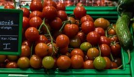 Merce nel carrello dei pomodori ciliegia in supermercato, vista in prima persona immagini stock