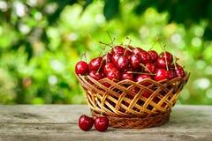 Merce nel carrello delle ciliege sulla tavola in giardino Fotografia Stock Libera da Diritti