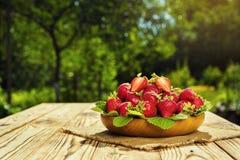 Merce nel carrello delle fragole sulla tavola di legno nello sfondo naturale, de Fotografie Stock
