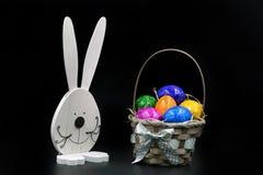 Merce nel carrello delle uova di Pasqua con coniglio su fondo nero Fotografia Stock