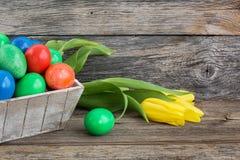 Merce nel carrello delle uova di Pasqua e tulipani gialli su fondo di legno Immagine Stock