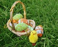 Merce nel carrello delle uova di Pasqua su erba verde Fotografia Stock