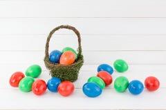Merce nel carrello delle uova di Pasqua su fondo di legno bianco fotografia stock
