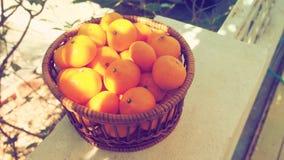 Merce nel carrello di piccola dimensione della frutta arancio sul recinto e sulla retro foto Fotografia Stock