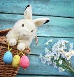 Merce nel carrello ed uova felici del coniglietto di pasqua su fondo blu Fotografie Stock Libere da Diritti
