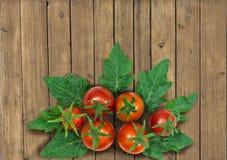 Merce nel carrello rossa fresca dei pomodori su fondo di legno Fotografie Stock