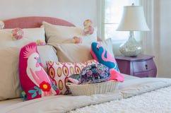 Merce nel carrello variopinta del cappello con i cuscini sul letto del bambino fotografie stock