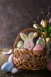 Merce nel carrello variopinta del coniglietto delle uova di Pasqua e dei biscotti e fiori dei tulipani sulla tavola di legno Fotografia Stock