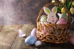 Merce nel carrello variopinta del coniglietto delle uova di Pasqua e dei biscotti e fiori dei tulipani sulla tavola di legno Fotografia Stock Libera da Diritti