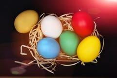 Merce nel carrello variopinta delle uova di Pasqua con il nido della paglia sul nero Fotografia Stock Libera da Diritti