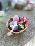 Merce nel carrello variopinta delle uova di Pasqua e dei fiori della molla sul fondo della tela da imballaggio fotografie stock libere da diritti