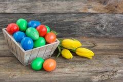 Merce nel carrello variopinta delle uova di Pasqua e tulipani gialli immagine stock libera da diritti