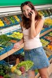 Mercearia - mulher de sorriso com telefone móvel Fotografia de Stock Royalty Free