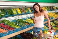Mercearia - mulher nova com telefone móvel Imagem de Stock